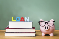 piggy bank wearing glasses next to books that have loan on them