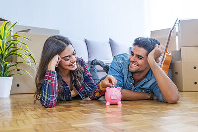smiling-couple-with-piggybank-new-home