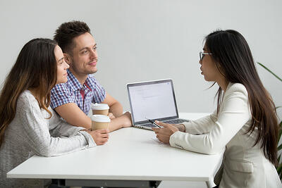 smiling-millennial-couple-listening-to-asian-advisor-lawyer-consulting-customers